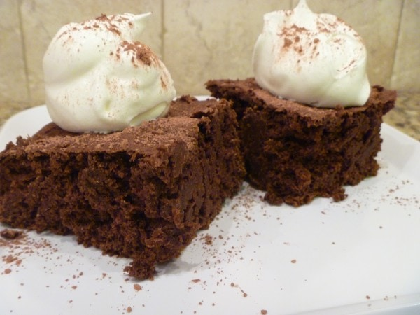 A piece of pumpkin chocolate cake on a plate with whipped cream