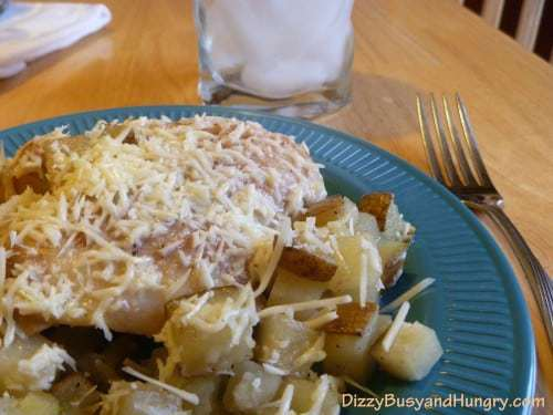 Close up view of baked chicken and potatoes sprinkled with cheese on a blue plate with a glass of water and a fork in the background.