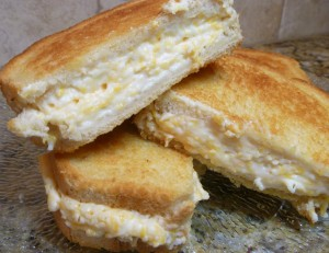 Side view of halved grilled cheese sandwiches stacked on each other.