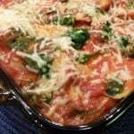 Close up shot of ravioli bake in pan with a blue background.