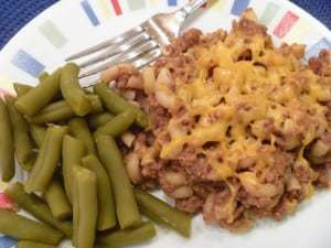 Overhead view of hamburger Mac and cheese and green beans on a white plate with a fork.