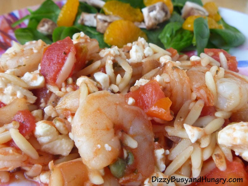 Close up shot of Greek shrimp with Orzo on a white plate.