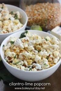 Close up shot of cilantro lime popcorn in a white bowl with a brown background.