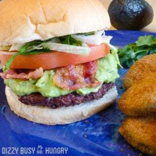 Close up shot of avocado bacon burger on a blue plate with an avocado and herbs in the background.