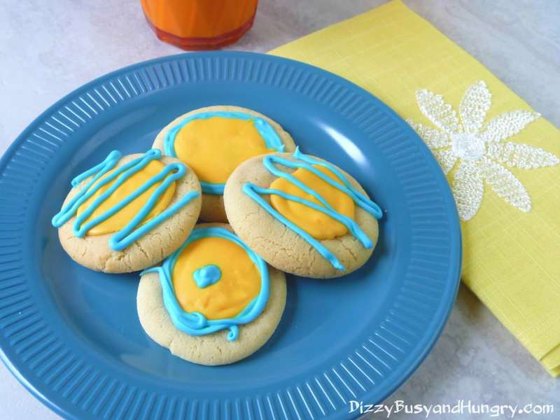 Overhead shot of four sunny citrus cookies on a blue plate with a yellow cloth on the side.