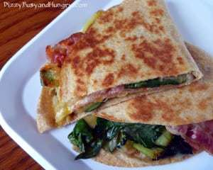 Overhead shot of stacked zucchini bacon cheese quesadillas on a white plate.
