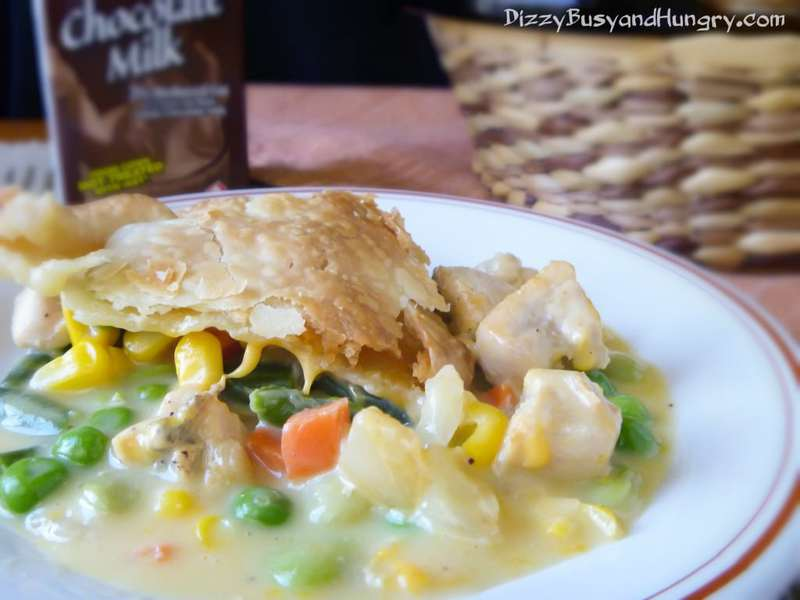 Side view of chicken pot pie slice on a white plate with a whicker basket in the background.