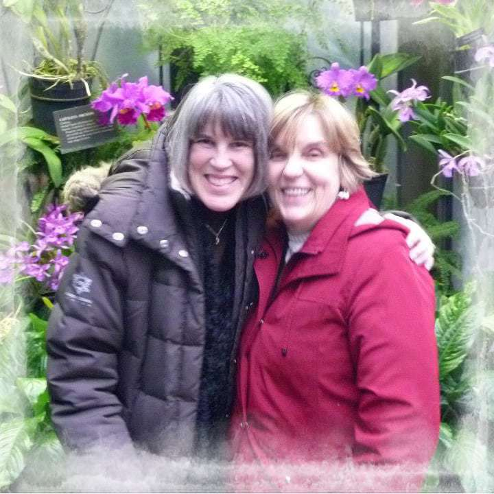 Two women posing for the camera with flowers in the background.