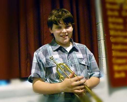 A close up shot of a boy holding a trumpet smiling at the camera.
