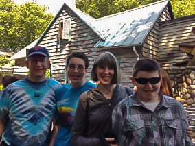 A man, woman, and two teenage boys posing in front of an outdoor cabin.