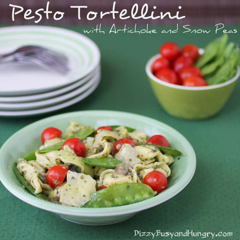 Side view of pesto tortellini in a green bowl with side of tomatoes and snow peas in the background on a green cloth.
