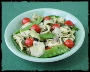 Side view of pesto tortellini in a green bowl on a green cloth.