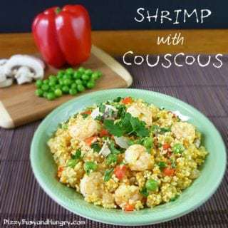 Side view of shrimp with couscous in a green bowl with a red bell pepper, mushrooms, and peas in the background.