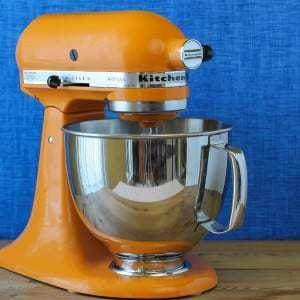 Close up shot of an orange Kitchen Aid mixer.