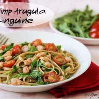 Side view of shrimp arugula linguine in a white bowl on a red cloth with a bowl of arugula and tomatoes in the background.