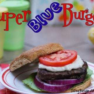 Side view of super blue burger with top bun leaning on a white plate.