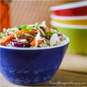 Side view of ramen noodle coleslaw in a blue bowl with more colorful bowls in the background.