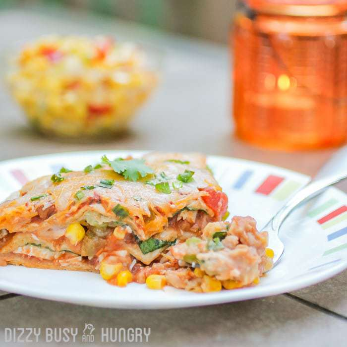 Fiesta Lasagna | DizzyBusyandHungry.com - Layered whole wheat tortilla casserole with refried beans, chicken, salsa, and lots of melted cheese!