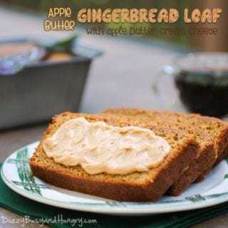 Side view of three slices of apple butter gingerbread loaf with apple butter cream cheese spread on the front stacked on a white plate with a cup of coffee in the background.