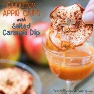 Side view of cinnamon apple chip being dipped into salted caramel dip with apples in the background.