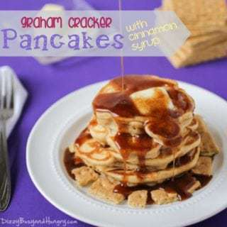 Side view of syrup being poured on graham cracker pancakes topped with butter on a white plate, with graham crackers and a fork in the purple background.