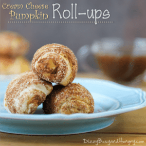 Side view of three cream cheese pumpkin rollups stacked on a blue plate on a wooden table.