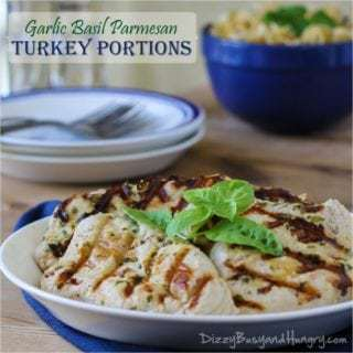 Side view of garlic basil parmesan turkey garnished with basil on a white plate with more plates in the background on a wooden table.