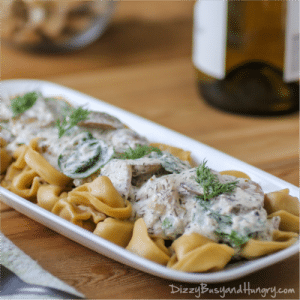 Side view of tortellini with greek yogurt and mushroom sauce on a white rectangle plate on a wooden table.