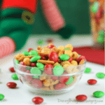 Side view of elf nibbles in a clear bowl with red and green MnMs sprinkled around.