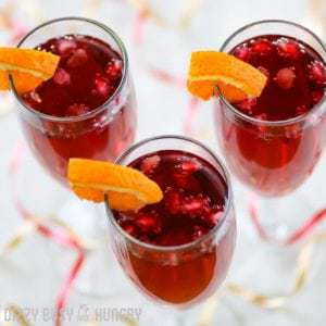Overhead shot of three pomegranate orange spritzer cocktails in champagne glasses with a sliced orange around the rim with red and yellow ribbon.