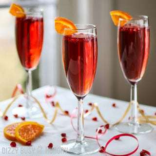 Side view of three pomegranate orange spritzers in champagne glasses with sliced orange on the rim with red and yellow ribbon on the white table.