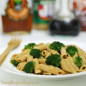 Side shot of broccoli penne with spicy peanut butter sauce on a white plate with a wooden fork on the side.