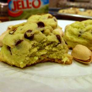 Close ups shot of pistachio chocolate chip cookies with a bite taken out on a white plate.