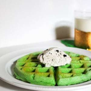 Side view of St. Patty's waffle cake with mint chocolate chip ice cream on a white plate.