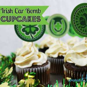Side shot of multiple Irish car bomb cupcakes with shamrock skewers.
