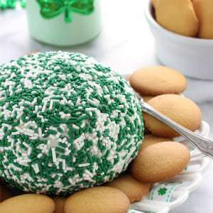 Close up shot of minty shamrock cheese ball surrounded by Nilla wafers on a white plate.
