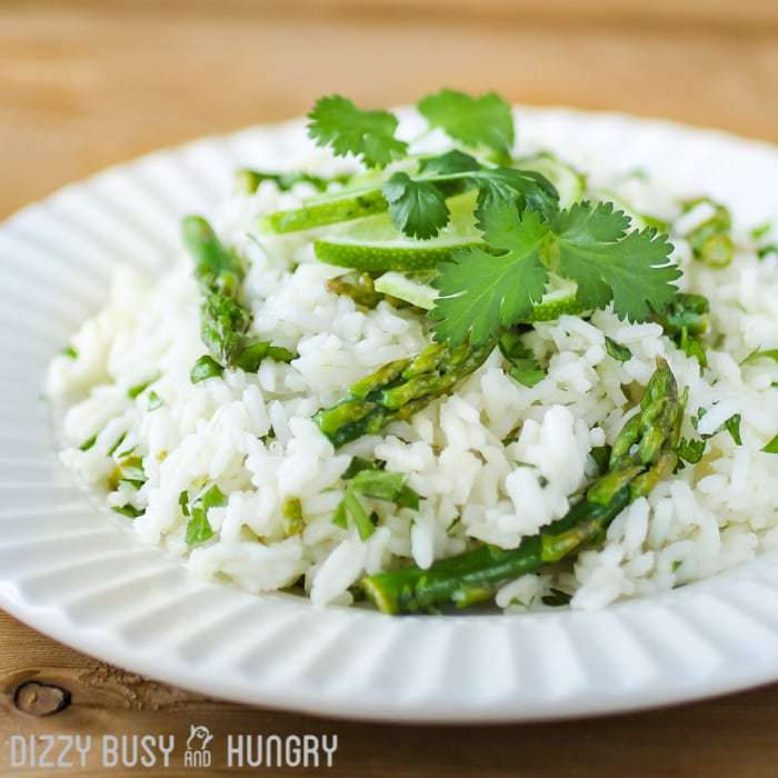Close up shot of cilantro lime asparagus and rice garnished with cilantro in a white bowl on a wooden table.