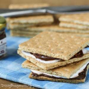 Side shot to two lunchbox S'mores stacked on a blue plaid cloth with more graham crackers in the background.