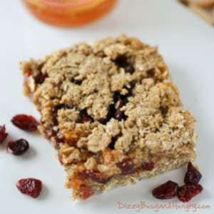 Close up shot of whole grain cranberry apricot bar on a white plate with cranberries sprinkled around.
