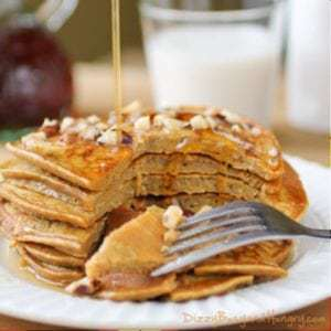 Side shot of pumpkin apple butter pancakes stacked on a white plate with a piece taken out with a fork.