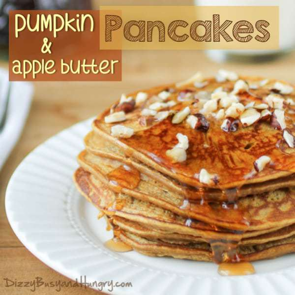Side shot of pumpkin apple butter pancakes garnished with syrup and nuts on a white plate on a wooden table.