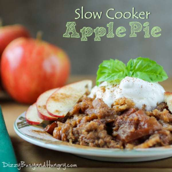 Close up shot of a slice of slow cooker apple pie garnished with sliced apples on green and white plate with apples in the background.