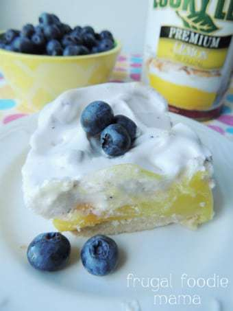 Close up shot of lemon blueberry meringue bar garnished with blueberries on a white plate with a yellow bowl of blueberries in the background.