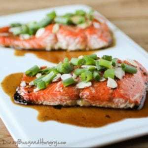 Side shot of two maple glazed salmon pieces garnished with almonds and chives on a white plate.