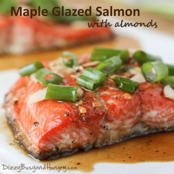 Side view of cooked salmon with maple glaze and garnished with sliced almonds and scallions.