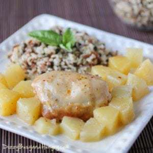 Side view of slow cooker pineapple chicken on a white square plate with a brown background.