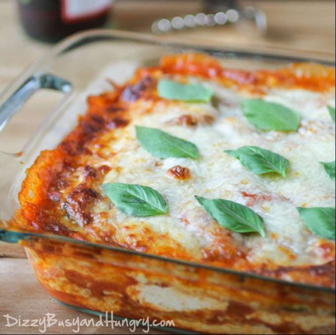 Side view of eggplant polenta lasagna in a clear pan with basil on top.