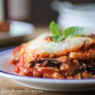 Side view of eggplant polenta lasagna garnished with herbs on a white and blue striped plate.