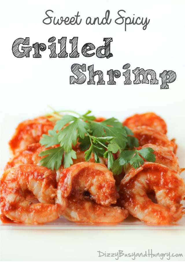 Close up shot of sweet and spicy grilled shrimp garnished with herbs on a white plate.