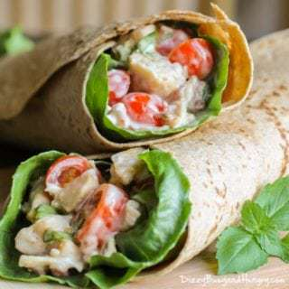 Side view of bacon blue cheese chicken wrap stacked on each other on a wooden surface.